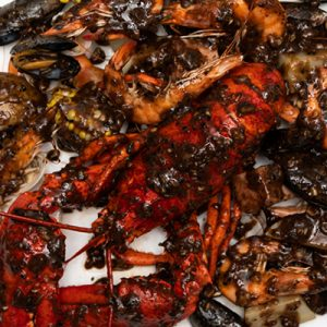 Hawaiian Cajun Lobster Combo with black pepper sauce.