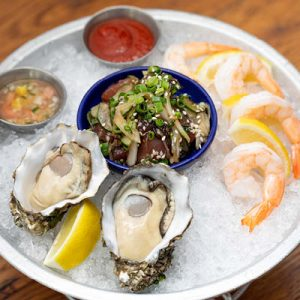 Chilled seafood sampler with raw oysters, shrimp cocktail and ahi poke.