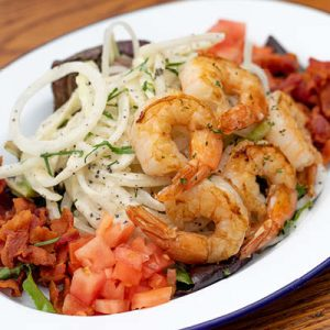 Mixed green salad served with sweet onion, tomato, bacon bits, vinaigrette dressing and grilled shrimp.