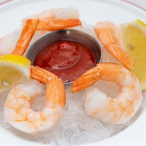 Five pieces of shrimp cocktail served on ice with savory cocktail sauce and a lemon slices.