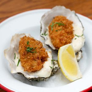 Two deep-fried oysters served in the shell with white sauce and a lemon slice.